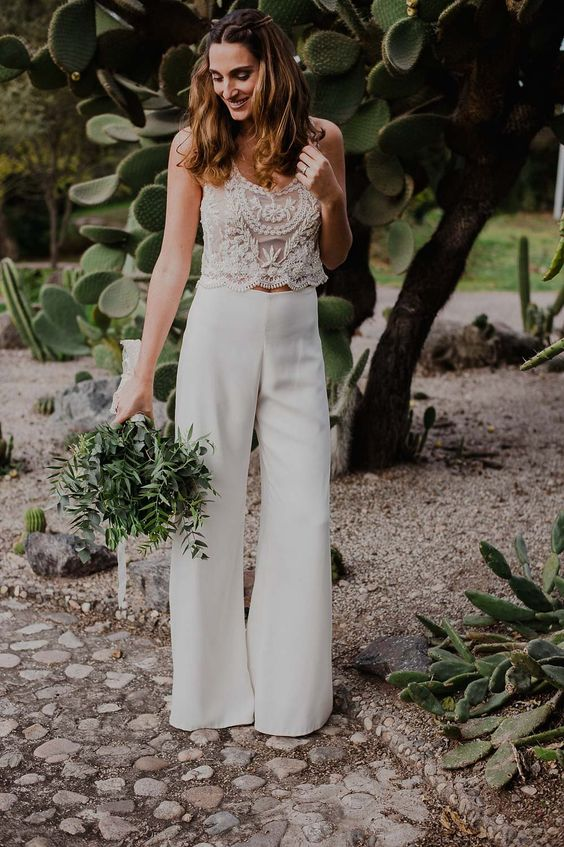 a bridal pantsuit with a cropped embellished lace top and plain pants to incorporate all the trends