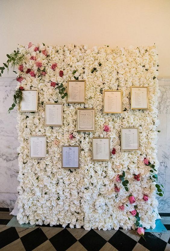 a gorgeous real rose wall in white and pink with frames that mean each table looks super glam