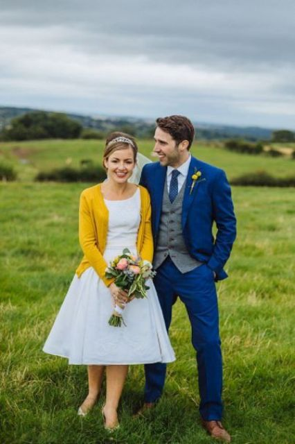a groom in a blue suit and a tie and a bride wearing a yellow cardigan - the beauty is in details