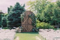 19 a rustic outdoor ceremony space with a large vintage door decorated with lush florals and greenery