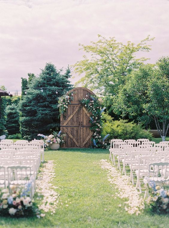 a rustic outdoor ceremony space with a large vintage door decorated with lush florals and greenery