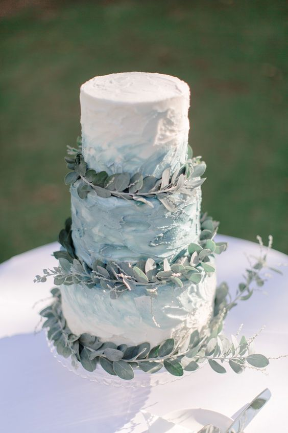a textural ombre buttercream wedding cake topped with eucalyptus for a chic look