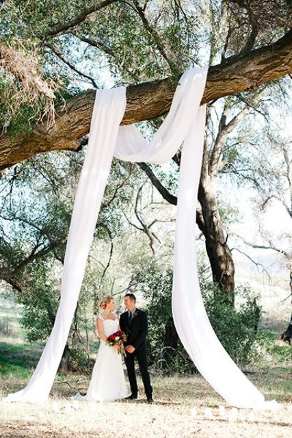 hang some ethereal white fabric on a tree branch to create an arch - nothing else is needed