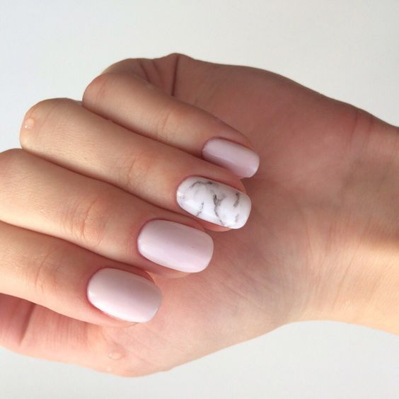 light pink matte nails and a white marble accent nail for a trendy feel in your look
