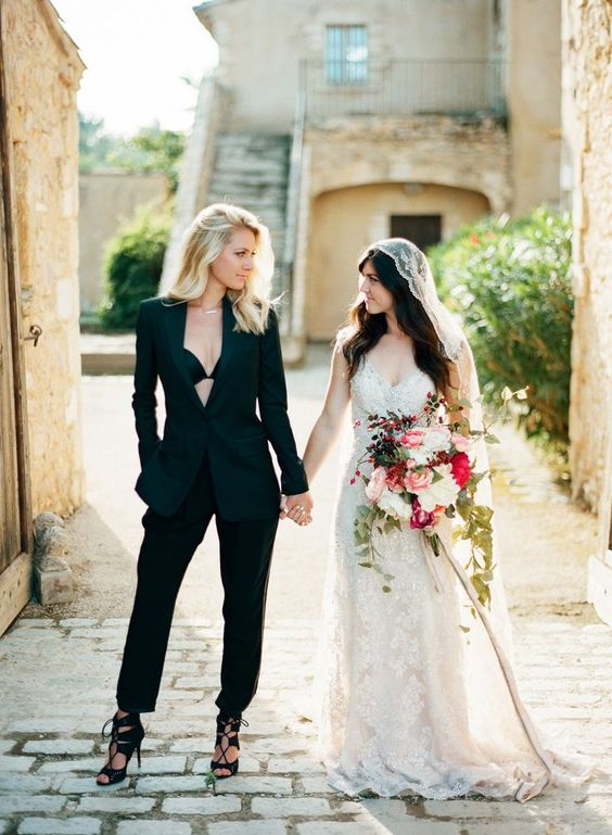a bride wearing a gorgeous black pantsuit with no top underneath and lace up heels for a wow effect