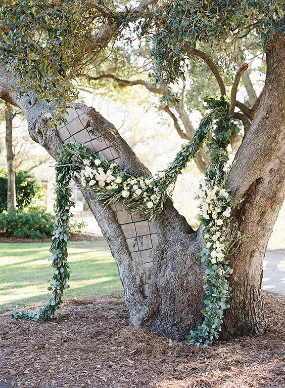 a large double tree with a luxurious greenery and white bloom garland for decor