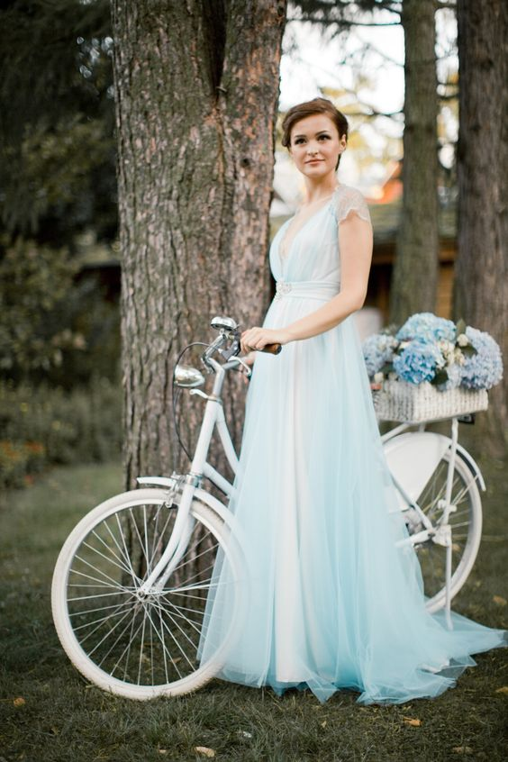a light blue wedding dress with lace cap sleeves, a deep V-neckline, a layered skirt looks very delicate