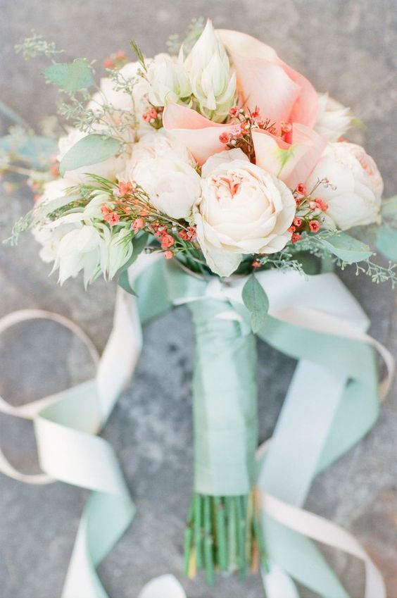 a peachy pink and ivory wedding bouquet with a mint wrap and ribbons