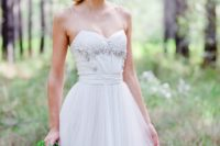 20 a white wedding dress with an embellished bodice, a sweetheart neckline and a pleated skirt