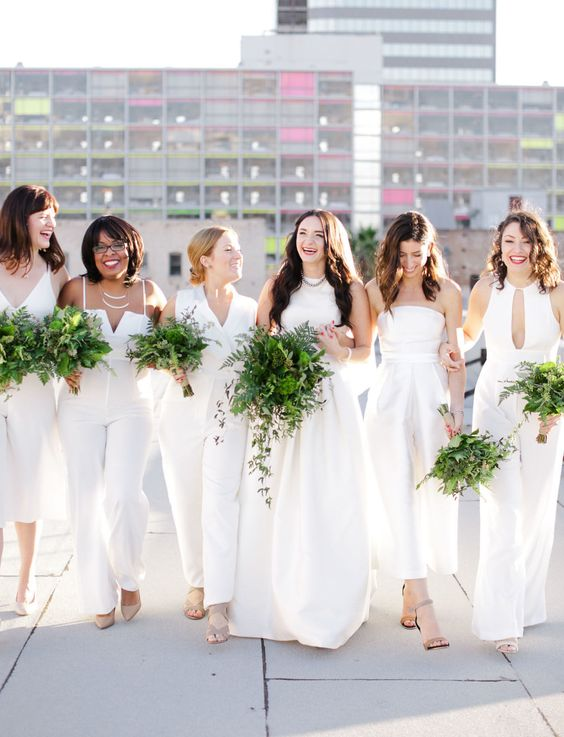 mismatching bridesmaids' jumpsuits in white and dresses for a trendy white bridal party look