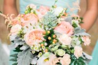 21 a bridesmaid wearing a strapless mint dress and a peachy pink and pale grey bouquet