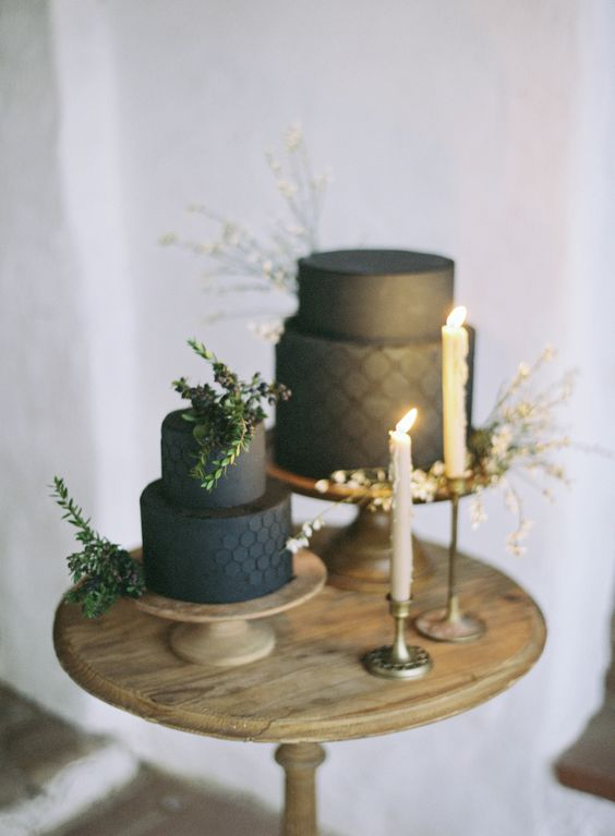 a couple of black textural wedding cakes with greenery on top for a minimalist wedding