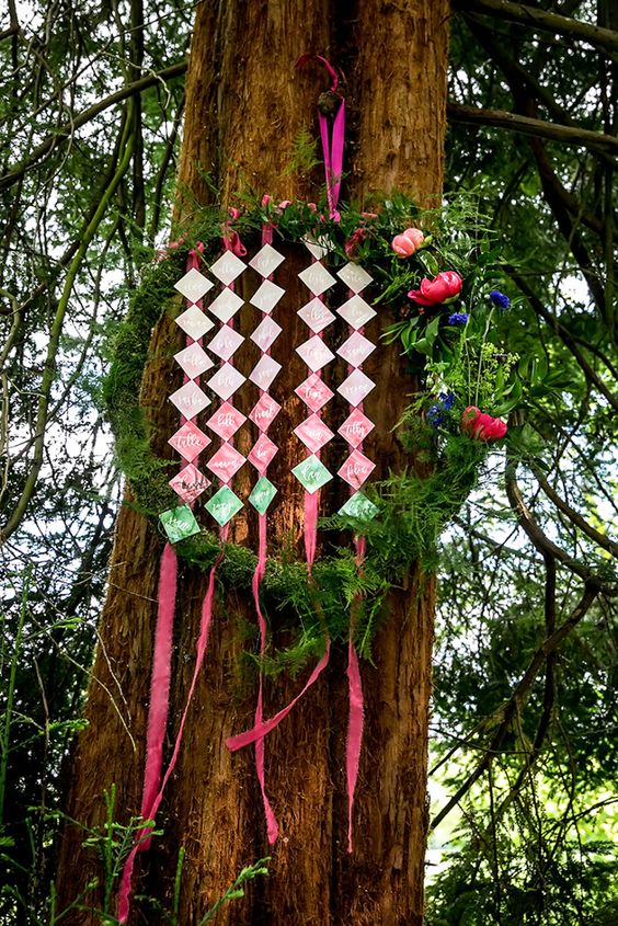 a moss and greenery covered wreath with bold blooms and ombre escort cards is a nice idea for a woodland fete