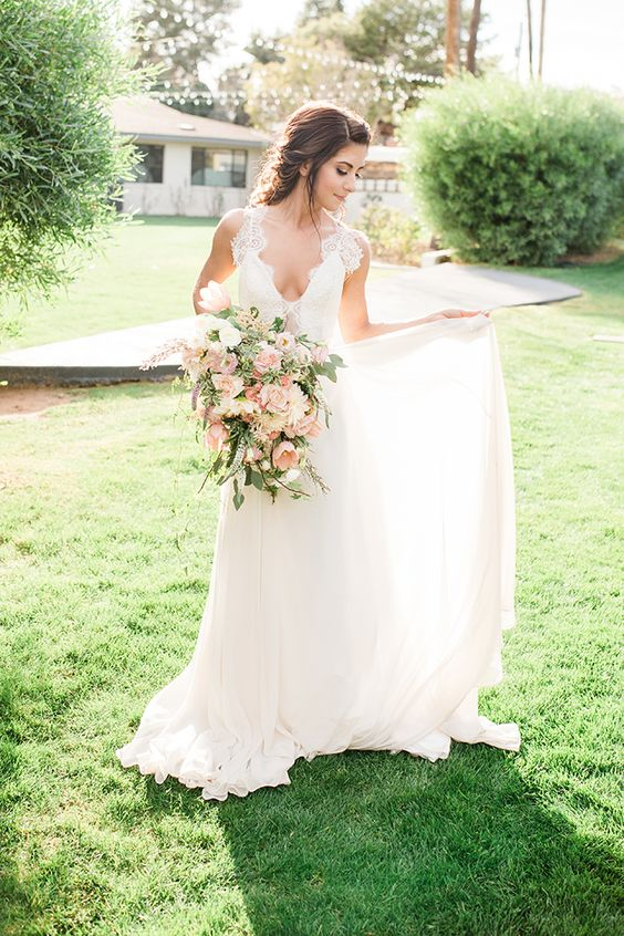 a romantic wedding gown with a deep neckline, thick lace straps, an embellished bodice and a flowy skirt