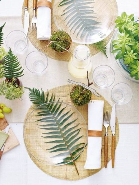 a woodland-themed wedding table with ferns, moss and greenery plus some wooden touches