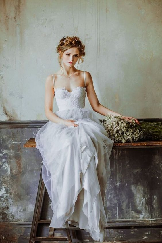 an A-line wedding dress with a lace bodice, a layered skirt and spaghetti straps