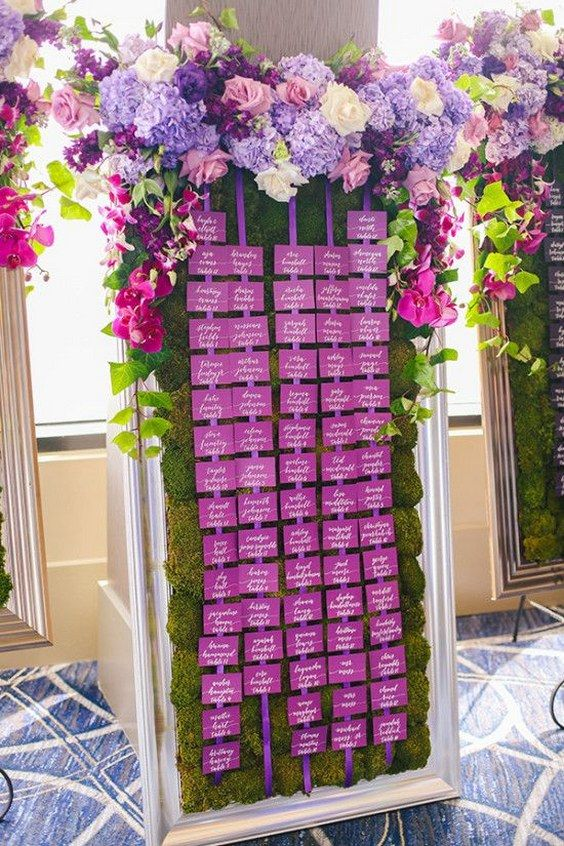 a real moss wall in a frame with a bold purple seating chart topped with very lush florals in lavender and purple colors