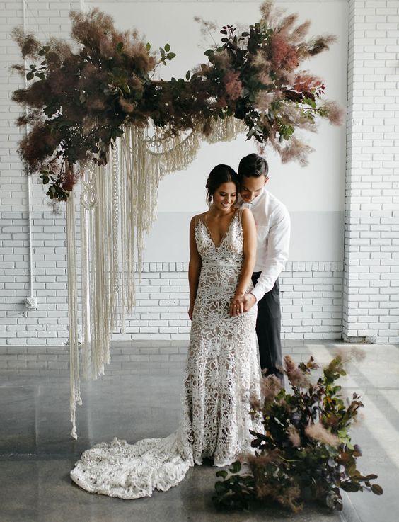 a semi sheer boho lace A-line wedding dress with a train and a deep V-neckline