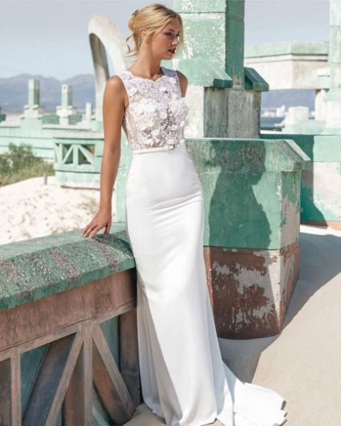a stunning sheath wedding dress with an pplique bodice and a thin white leather belt that separates the sleek skirt from it