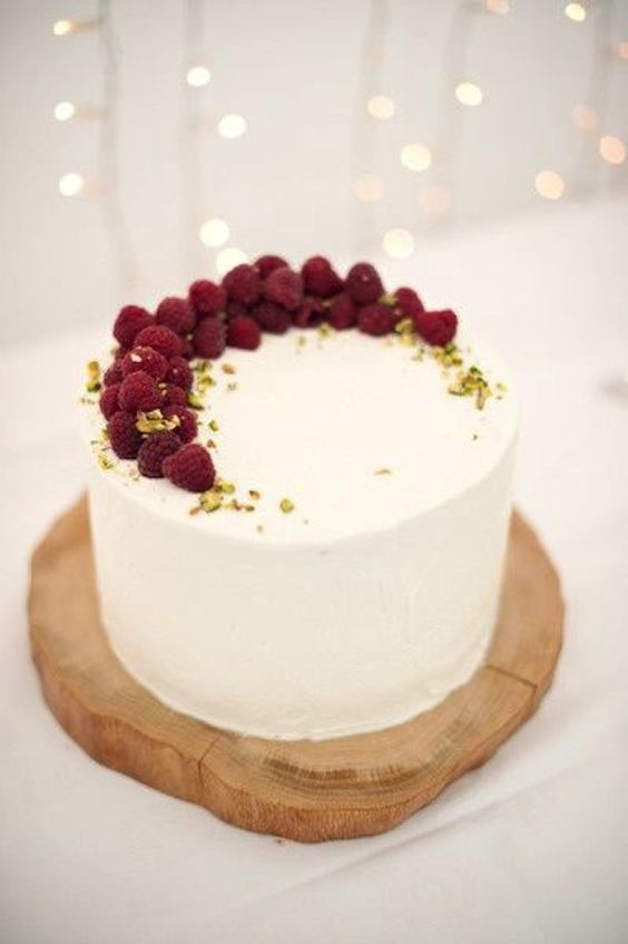 a white wedding cake with a crescent moon made of raspberries and pistachio petals