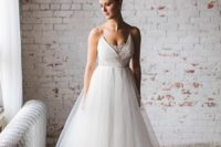 22 an A-line wedding dress with a wrap bodice, a lace neckline insert and a tulle skirt for a ballerina-inspired look