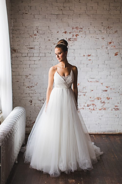 an A-line wedding dress with a wrap bodice, a lace neckline insert and a tulle skirt for a ballerina-inspired look