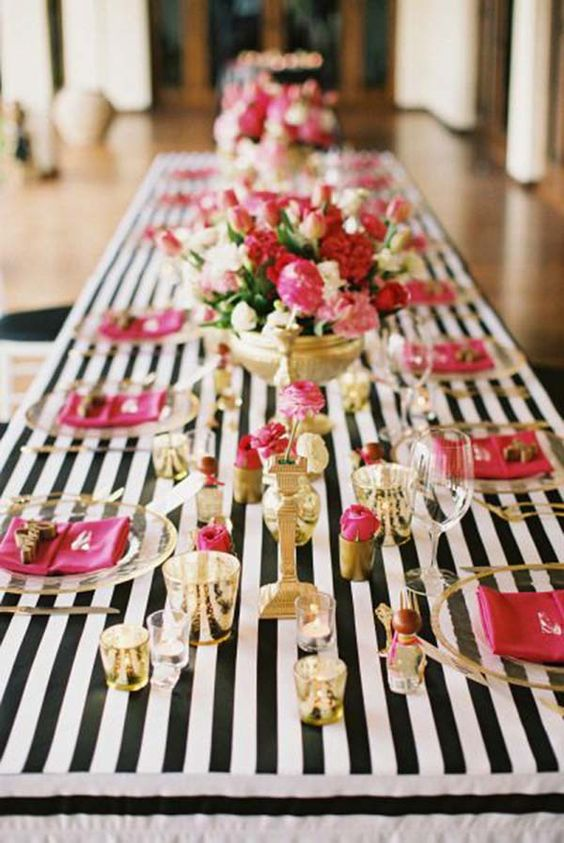 black, white and gold table setting spruced up with bold pink touches