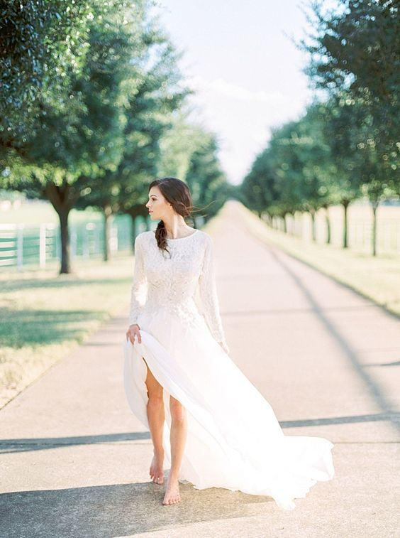 a modern bridal look with a lace high neckline wedding dress with long sleeves and a messy hairstyle