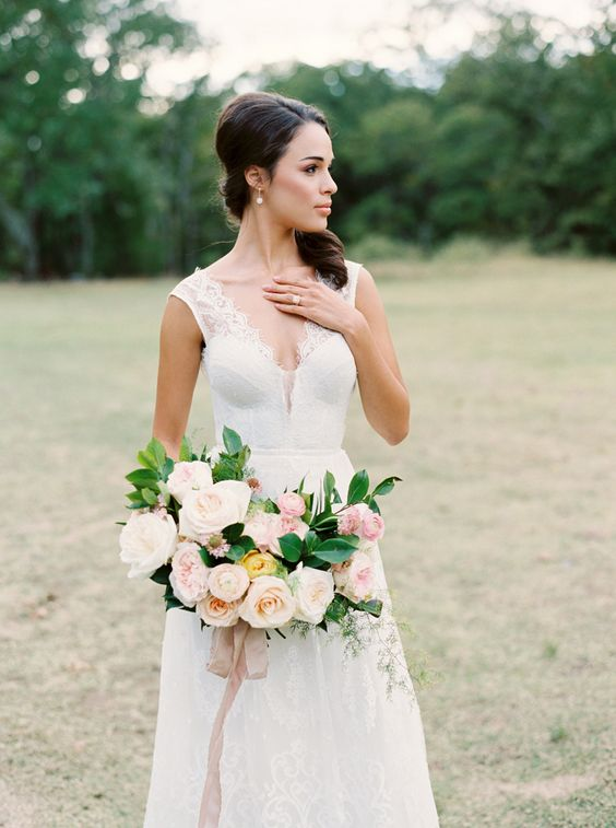 a stunning romantic lace wedding dress with thick straps, a covered plunging neckline, an A-line skirt