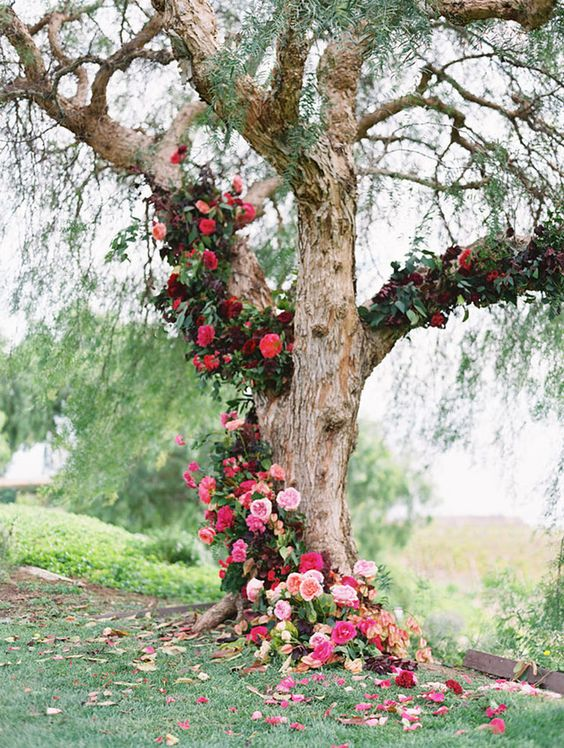 a tree covered with bold red, burgundy and pink blooms and greenery for a ceremony