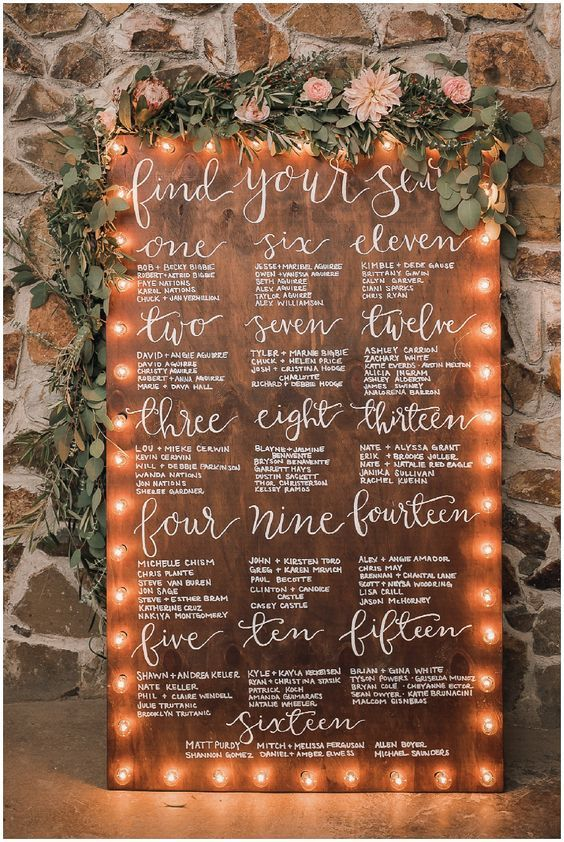 a wooden seating chart with white calligraphy and marquee lights and topped with fresh greenery and blush blooms
