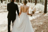 23 an A-line wedding dress with spaghetti straps that create eye-catchy geometry on the back