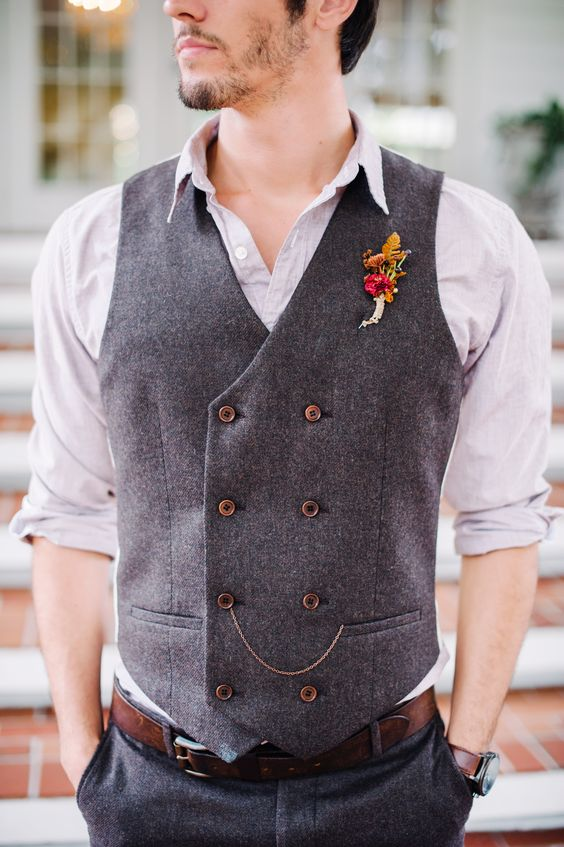 grey pants and a vest plus a light grey shirt, a chain and a colorful floral boutonniere
