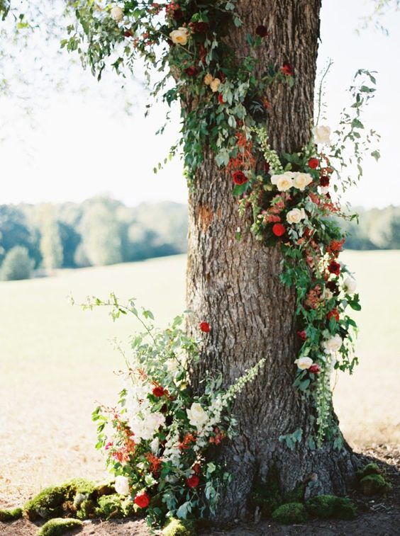 a tree decorated with bright floral posies in red and burgundy, with greenery for a fresh touch