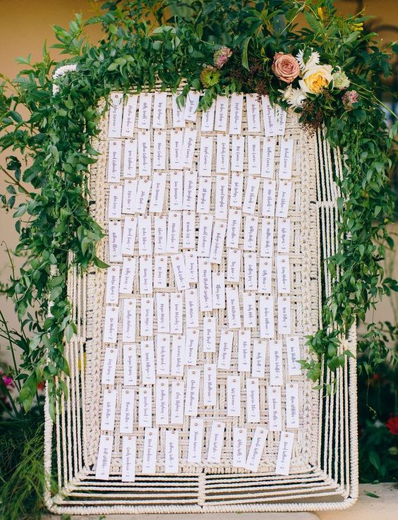 a woven tray with letter press escort cards attached and a lush greenery garland with blooms on top