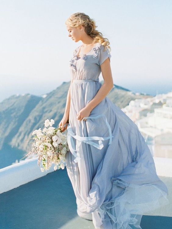 an airy light blue wedding dress with a V-neckline, floral lace appliques on the bodice and a sash
