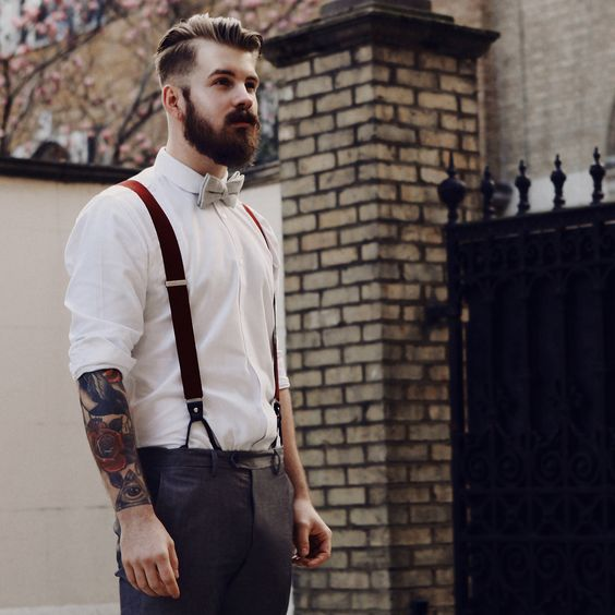 grey pants, a white shirt and rust-colored suspenders with a light-colored bow tie