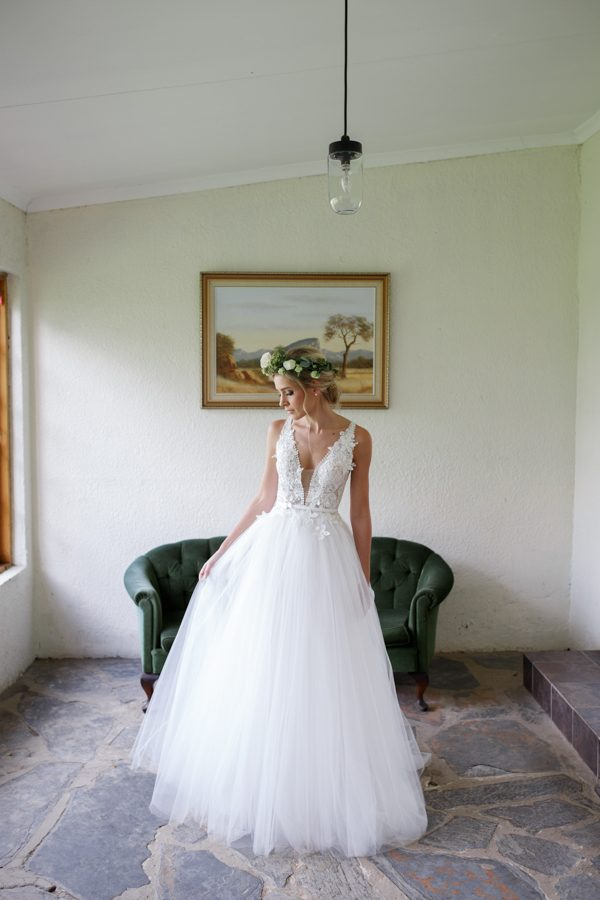 A line wedding dress with a bodice and thick straps decorated with floral appliques, a covered plunging neckline and a tulle skirt