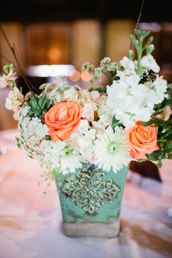 a mint colored vintage pot with whiote and peachy blooms and a texture