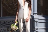 25 a pure white pantsuit with a sleeveless vest with a plunging neckline and pants, heels and minimalist earrings