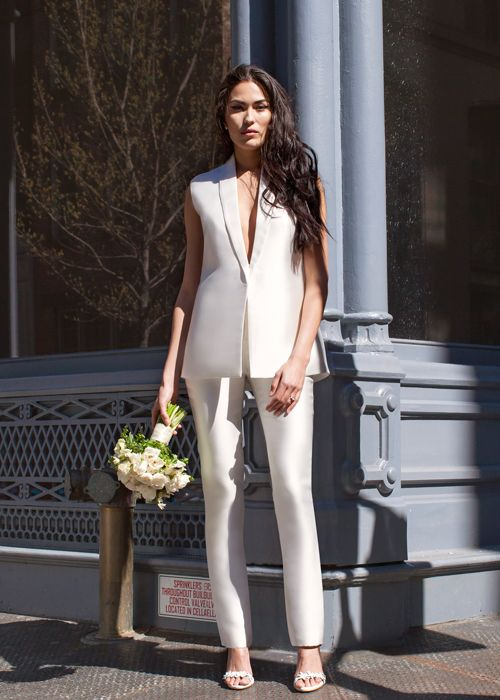 a pure white pantsuit with a sleeveless vest with a plunging neckline and pants, heels and minimalist earrings