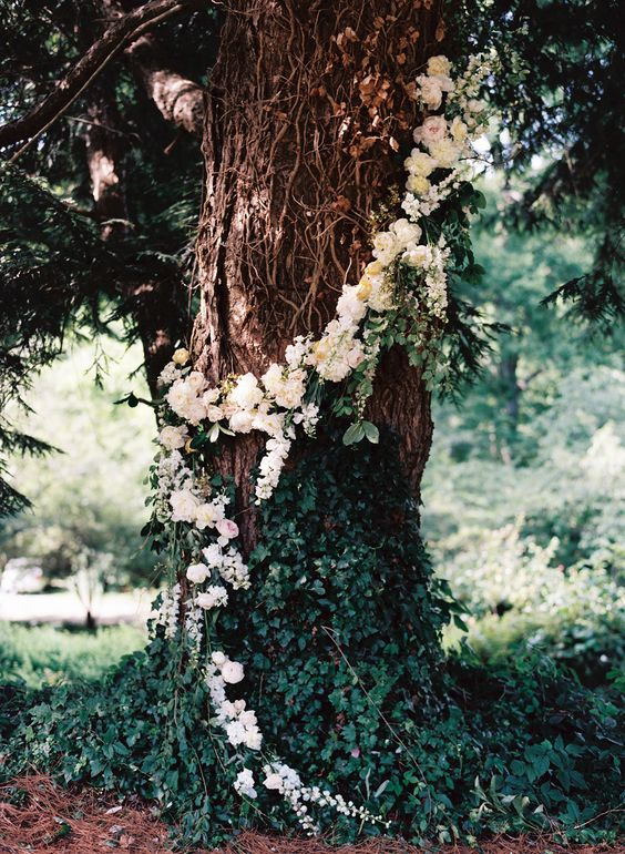 a tree fully covered with neutral florals and lush greenery can be used as a ceremony backdrop