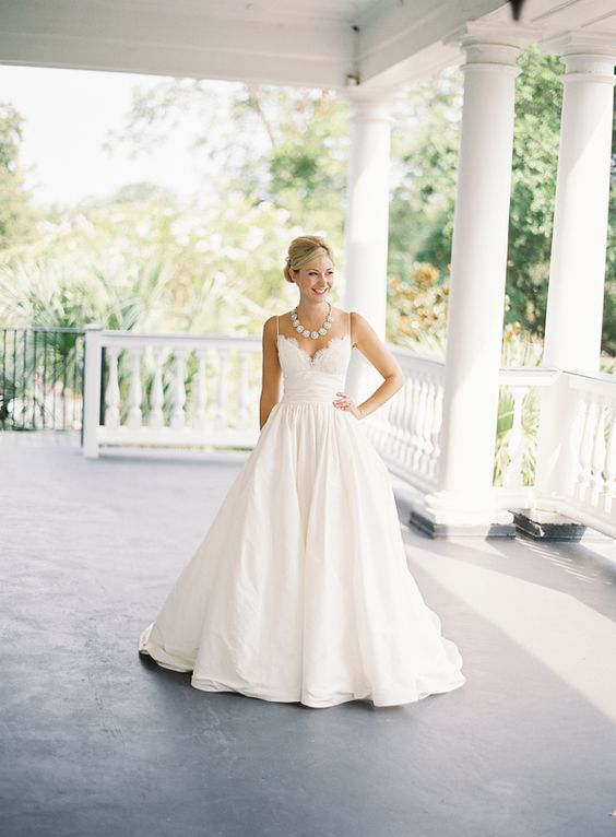 an A line wedding gown with a lacey bodice, a full skirt and a statement necklace to fit the neckline