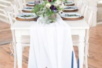 25 an ombre white and blue table runner with blue candles and contrasting blooms as centerpieces