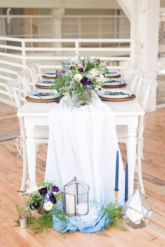an ombre white and blue table runner with blue candles and contrasting blooms as centerpieces