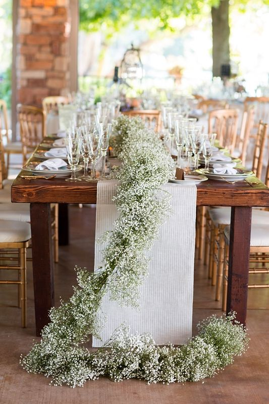 a baby's breath table runner over a neutral fabric one is a grea option for a rustic wedding