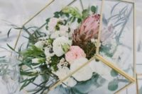 26 a large florarium centerpiece with blooms and greenery for a modern wedding