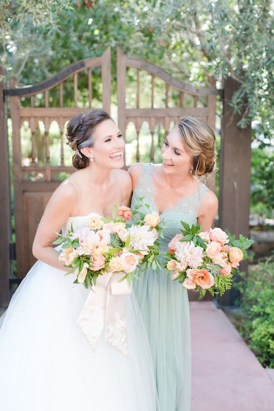 a mint wide strap bridesmaid dress and a peachy pink bouquet
