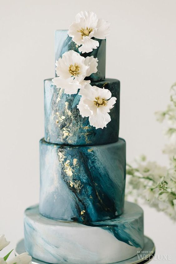 a stunning blue marble wedding cake with gold leaf and sugar white flowers on top