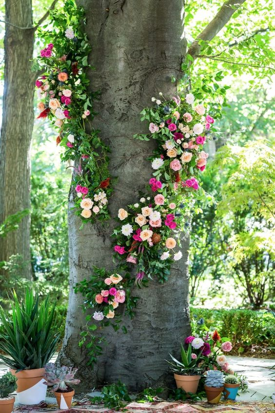 a tree wrapped with bold pink, blush and ivory blooms and greenery for a wedding ceremony